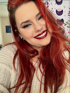 selfie of a young woman smiling with red hair and red lipstick